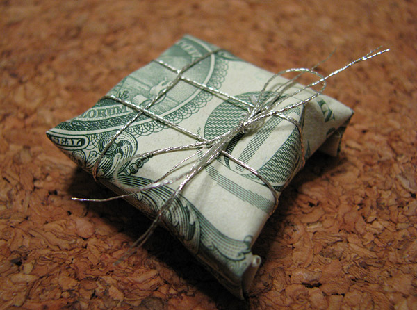 Photo: a tiny gift package, four quarters wrapped in a dollar bill